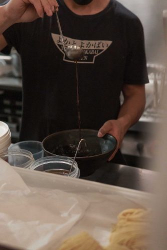 kitchen staff pouring ramen dashi